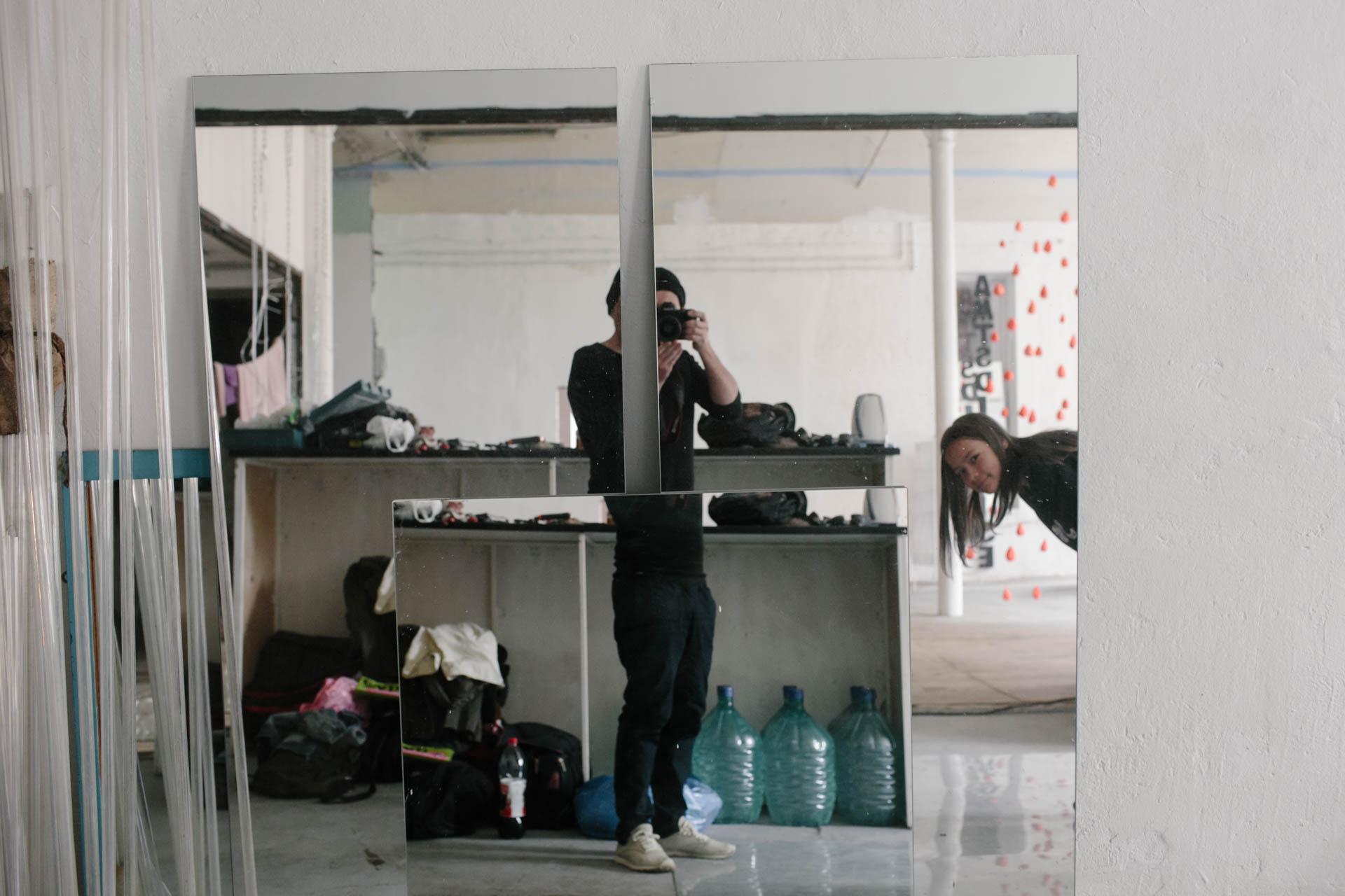 На фотографии я в отражении трёх зеркал. В кадр заглядывает Ульяна. У меня Canon в руках, на ногах Reebok, бутылки, сумки, стена. Это Москва. Это Артдепартамент. Мы в гостях и скоро пойдём гулять.