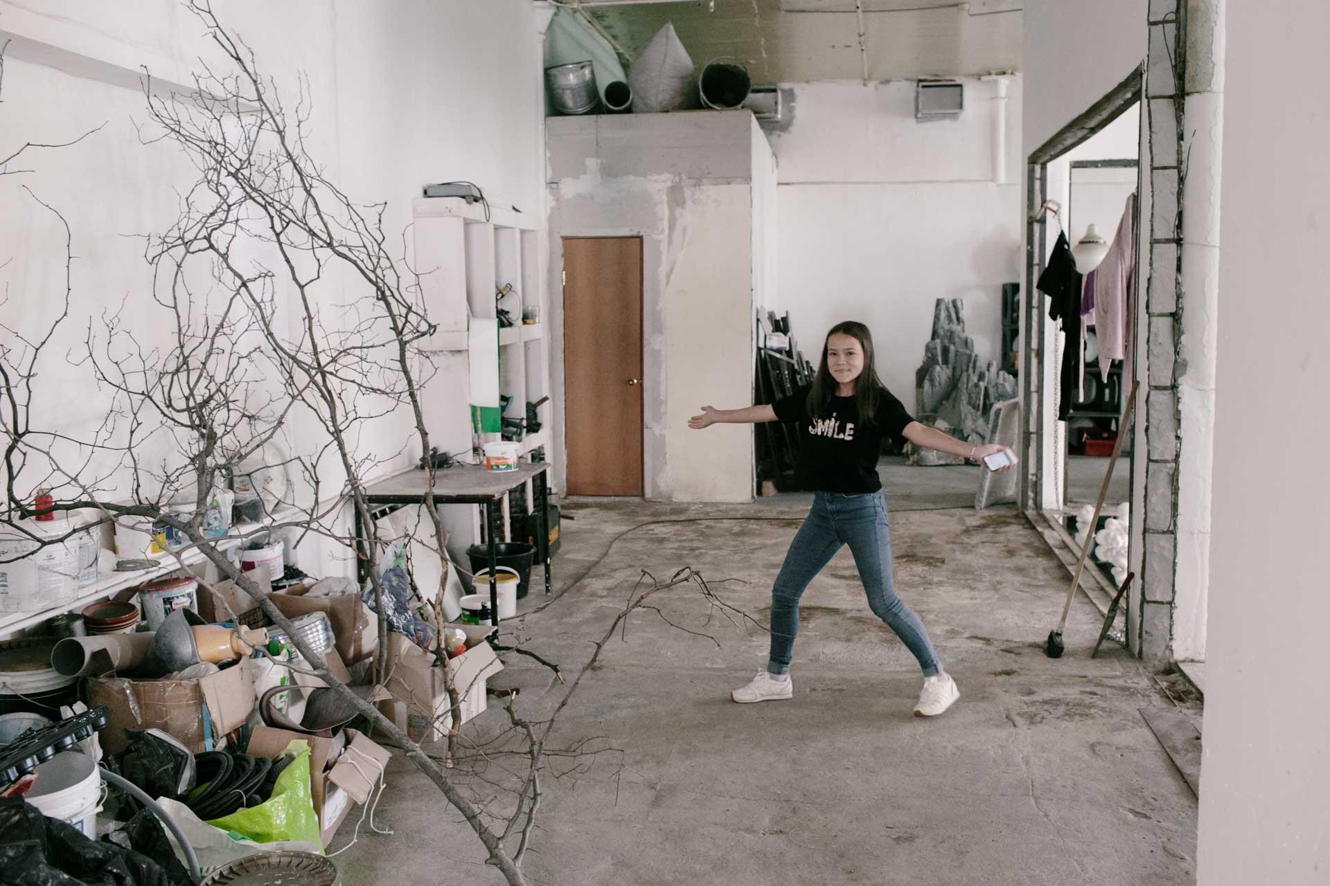 Ульяна улыбается. Это студия в Москве и мы гости. Делаю несколько фотографий интерьера. Сухой куст для декорации, нагромождение чего-то у стены, стеллажи с инструментами, сохнет белье. Так, выйди из кадра.