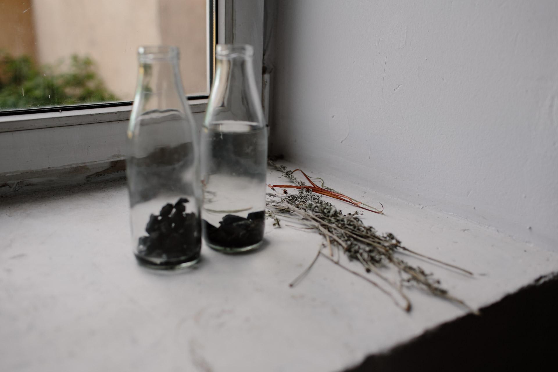 Вода в стеклянных бутылках для полива цветов