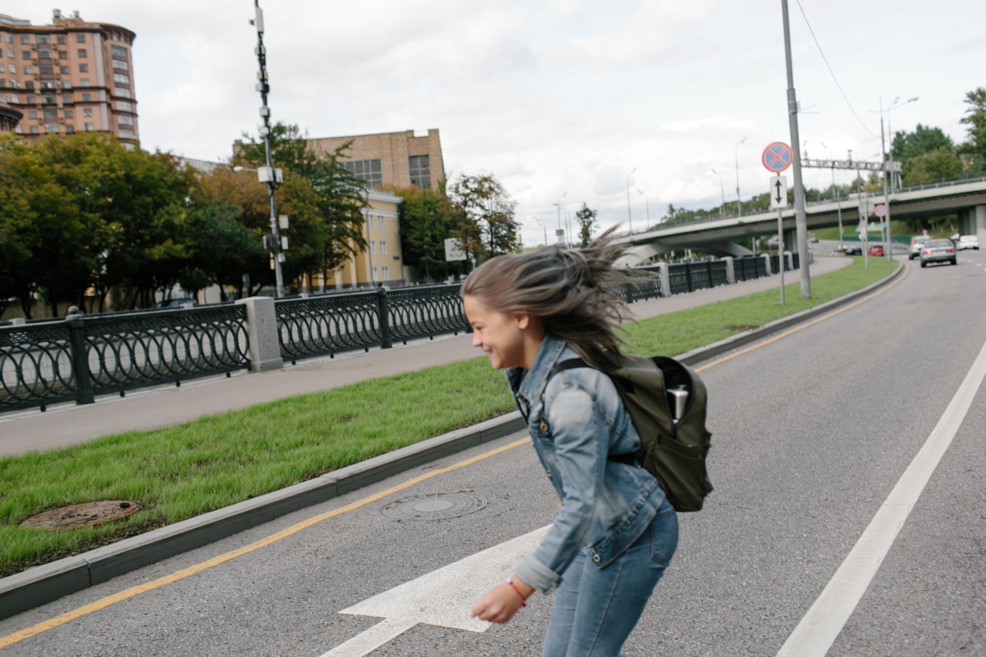 На фотографии Ульяна перебегает дорогу на набережной реки Яузы в Москве. Одностороннее движение, улыбка, джинсовая куртка и открытый рюкзак - сломана молния или плохо работает, я уже не помню. Мы пошли на прогулку по городу и скоро заболеем.