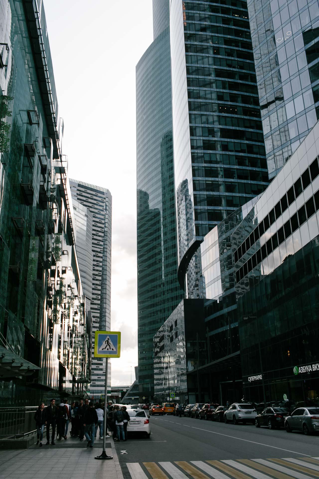 Это Москва. Конец лета, очень холодно. На фотографии улица в деловом центре. Пешеходный переход, знак пешеходного перехода, несколько человек на тротуаре возле белой машины. На другой стороне супермаркет «Азбука вкуса». Высокие стеклянные здания по обе стороны улицы.