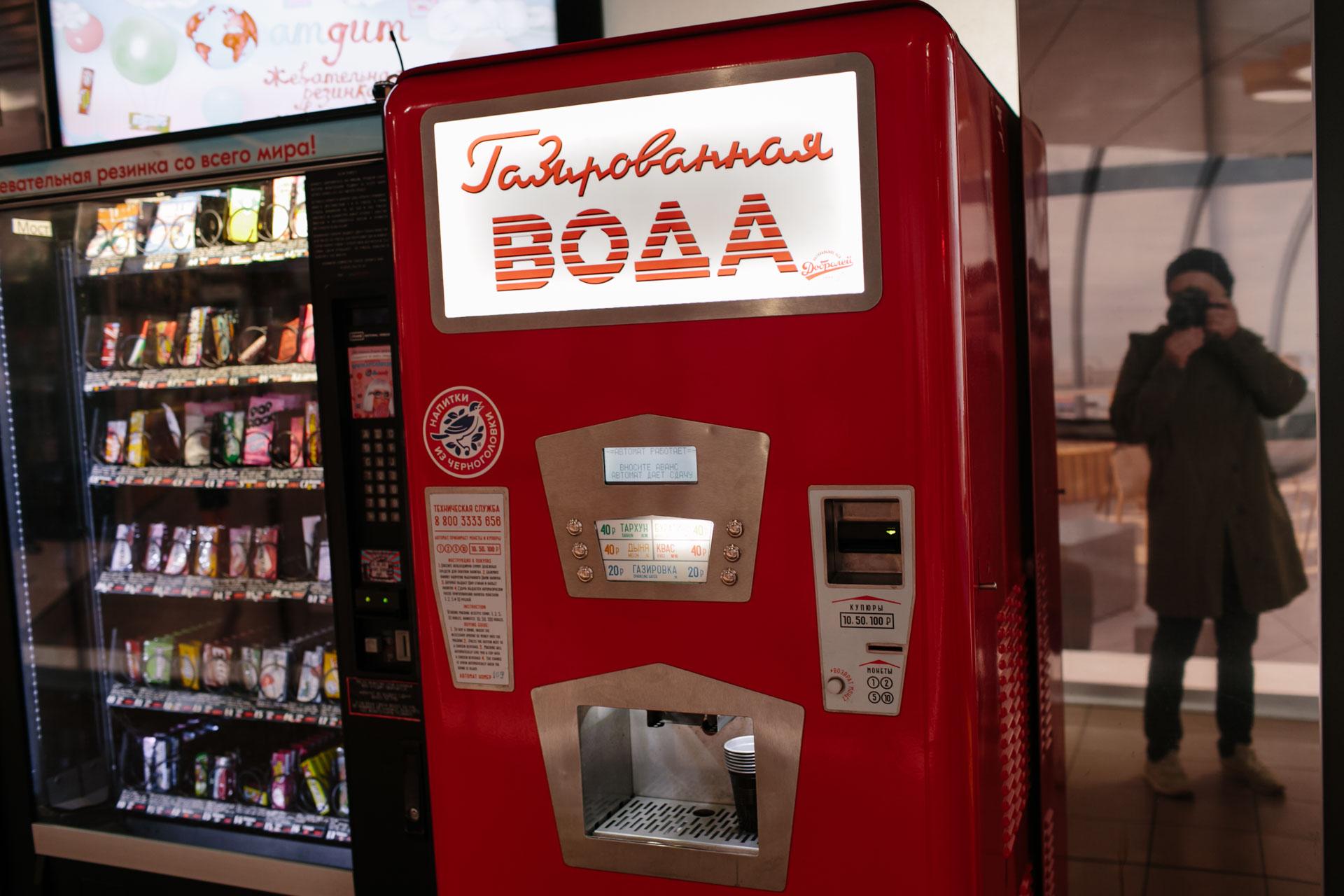 На фотографии автомат для продажи газированной воды. Принимает купюры и монеты один, два, пять и десять рублей. В отражении зеркала, рядом с автоматом, я с фотоаппаратом делаю эту фотографию. Москва.