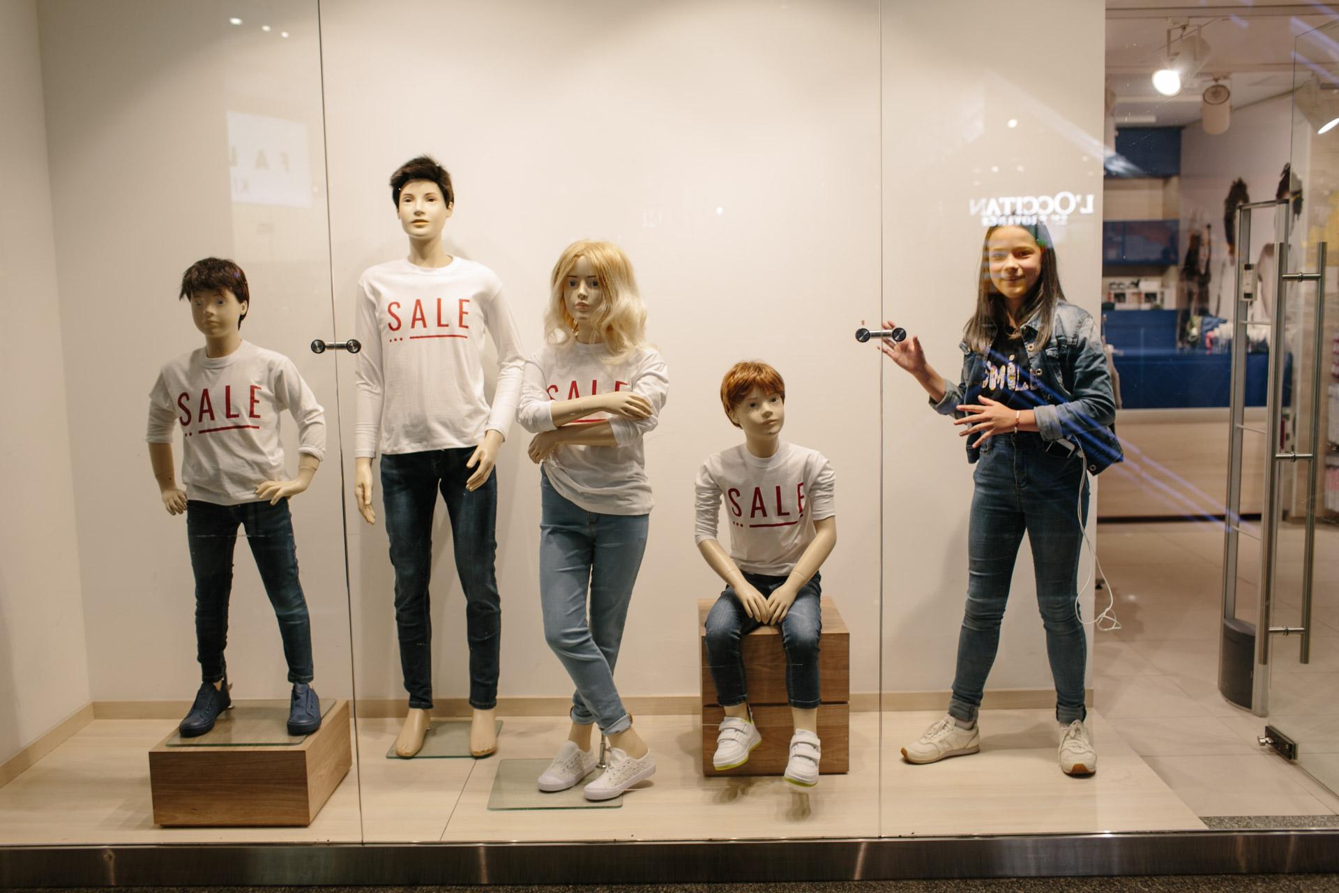 Это витрина магазина в торговом центре. Четыре манекена в белых футболках с надписями «SALE» и Ульяна делает вид, что она тоже манекен, но на ней джинсовая куртка и чёрная футболка с другой надписью. Чайник кипит.