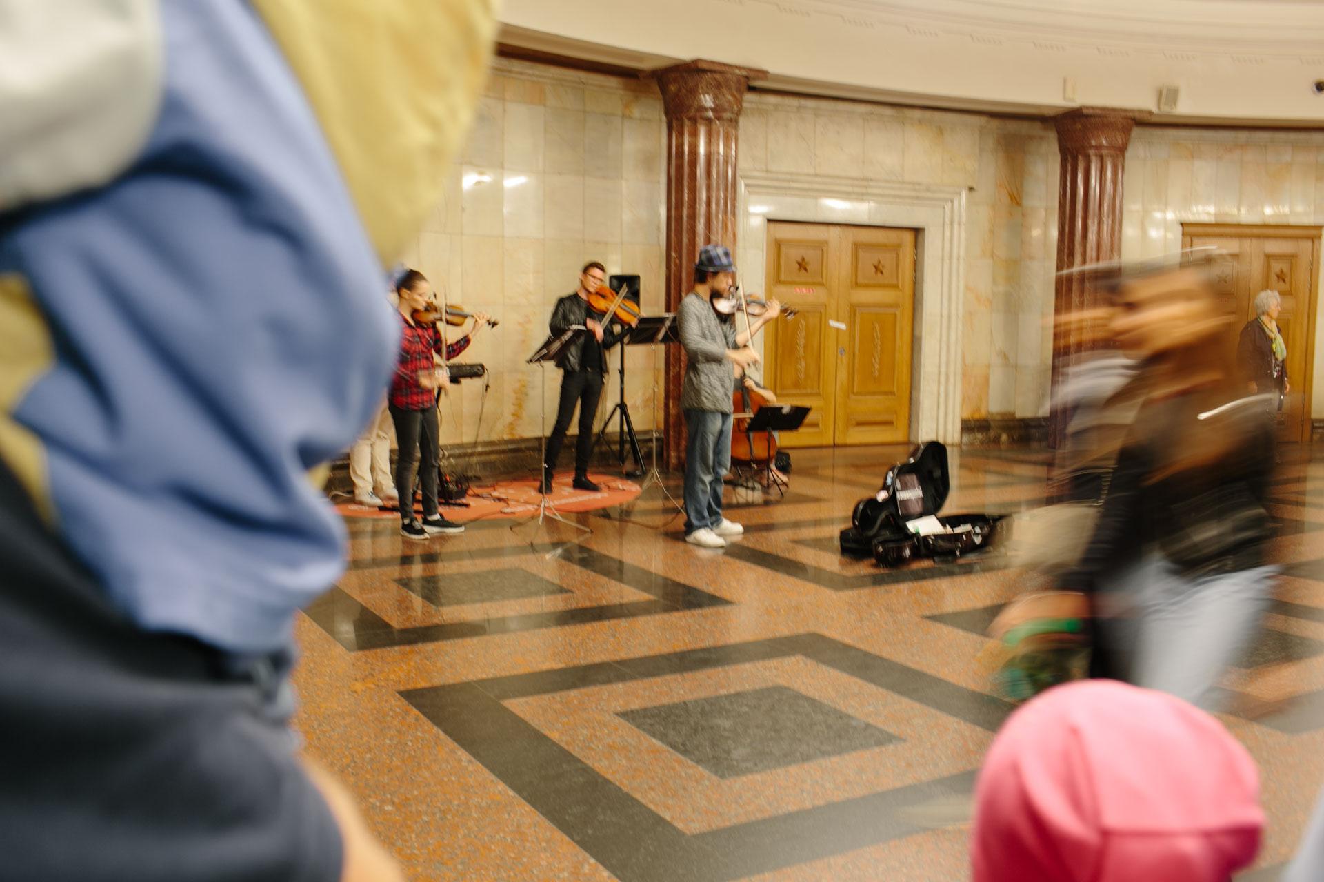Концерт в вестибюле станции метро «Курская», достаточно известное место. Это наша станция. Дальше мы идём пешком до дома, достаточно далеко. Скрипач на переднем плане, ещё двое сзади, ноги, видимо, ещё одного музыканта. Люди спешат, кто-то останавливается и слушает. Мы остановились и сделали эту фотографию. Пора заваривать чай.