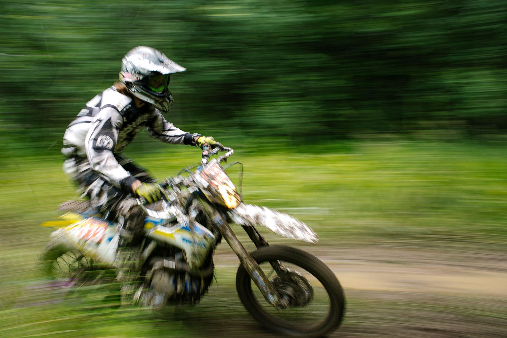 На фотографии мотоциклист на большой скорости едет по лесу. Спортивный мотоцикл, шлем, защита, номер - соревнования. Недалеко от Ярославля открытая тренировка, так называют соревнования летом 2020 года, по эндуро.