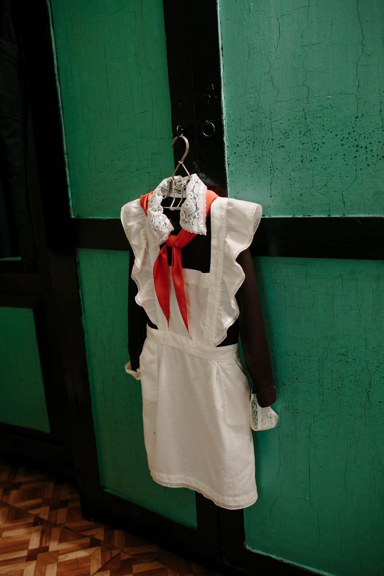 На фотографии школьная форма времён СССР: белый фартук, кружевные манжеты и воротничок, красный пионерский галстук. Весит на вешалке в помещении школьного музея в посёлке Судома Вельского района.