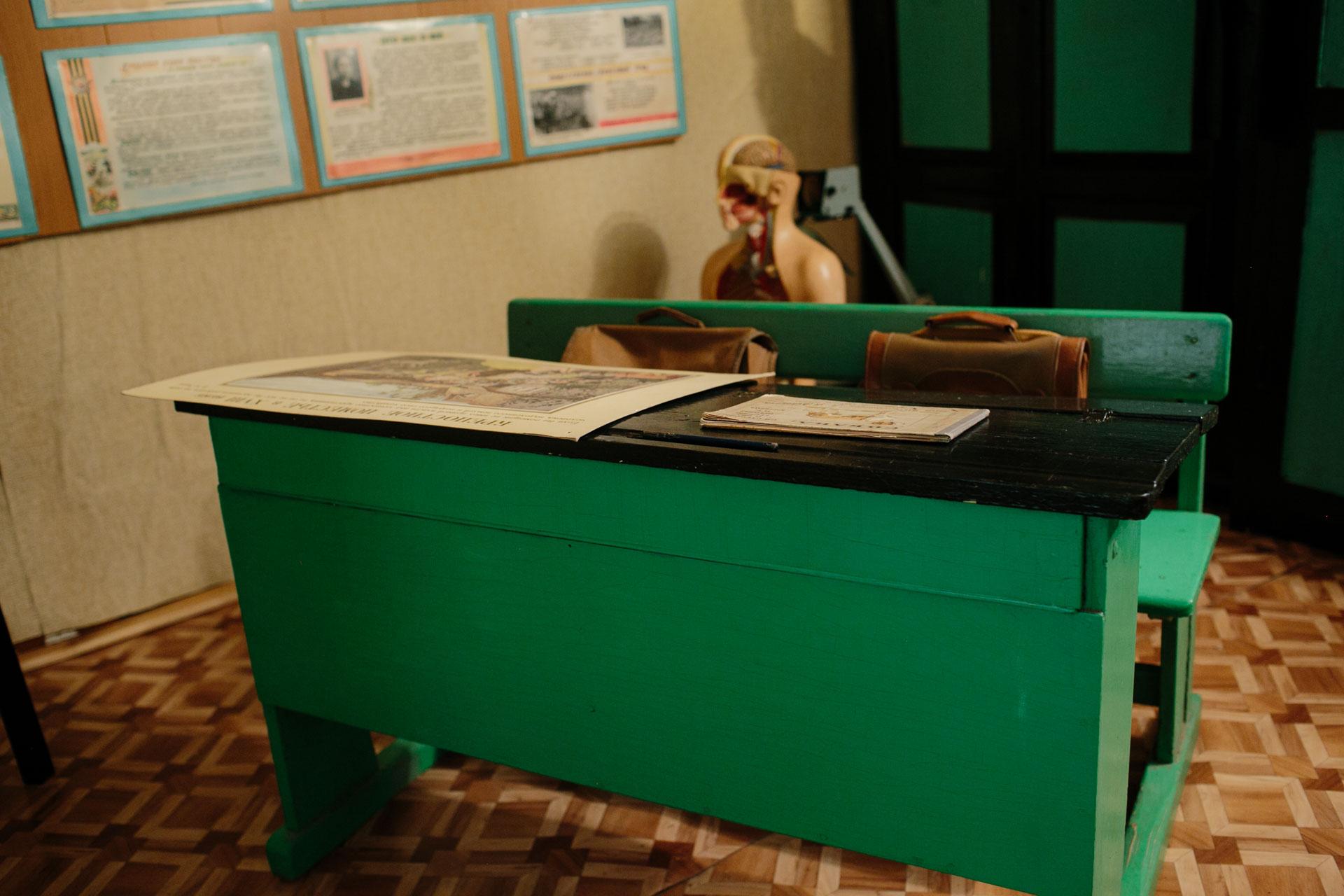 На фотографии школьная парта конца 20 века в советских, потом российских школах. Выкрашена в зелёный цвет уже не первый раз. Темная столешница под углом для удобства. На парте лежит карта, два ранца на месте для учеников. Находится в музее при школе № 13 посёлка Судома Вельского района.