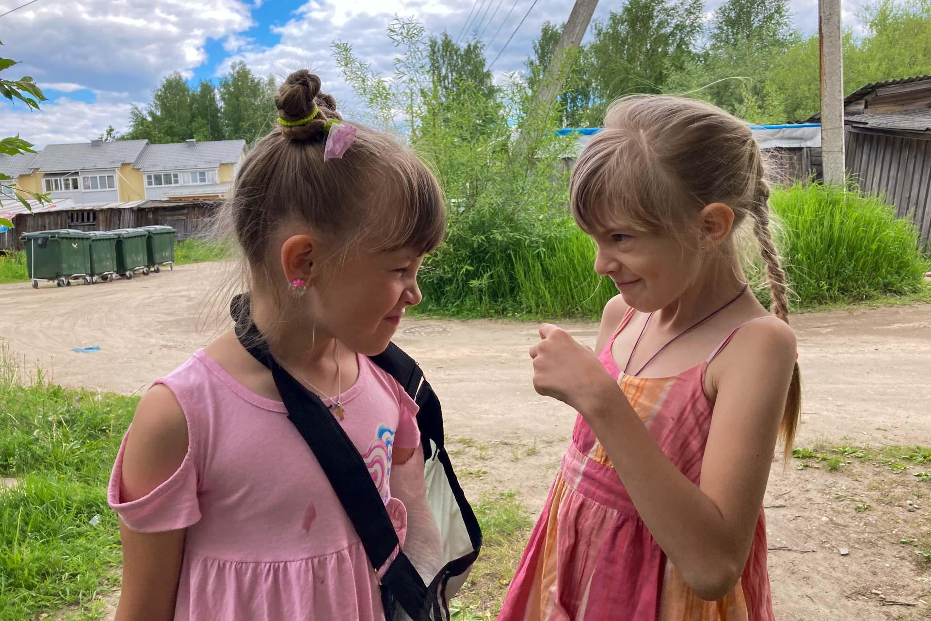 Обе в розовых платьях. На дворе лето 2021 года, самое начало июня. Жарко. Девочки смотрят друг на друга. Подруга показывает кулак Вари. У Вари гипс на левой руке после падения со школьного забора. Родители дома.