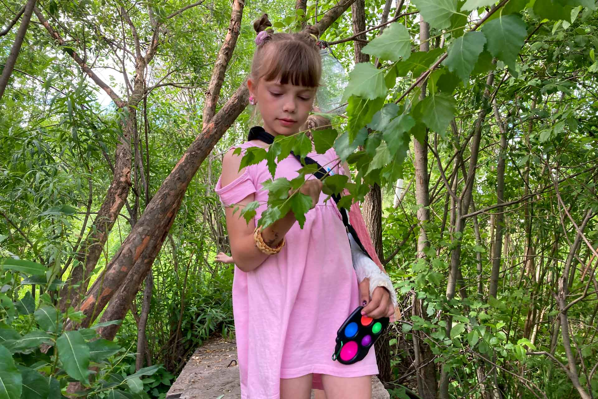 В сломанной руке Simple Dimple Among Us. На другой браслет из бересты, сделанный в школе. Розовое платье. На дворе лето 2021 года. Город Вельск, деревянный многоквартирный дом рядом со школой. Теплотрасса. Серги.