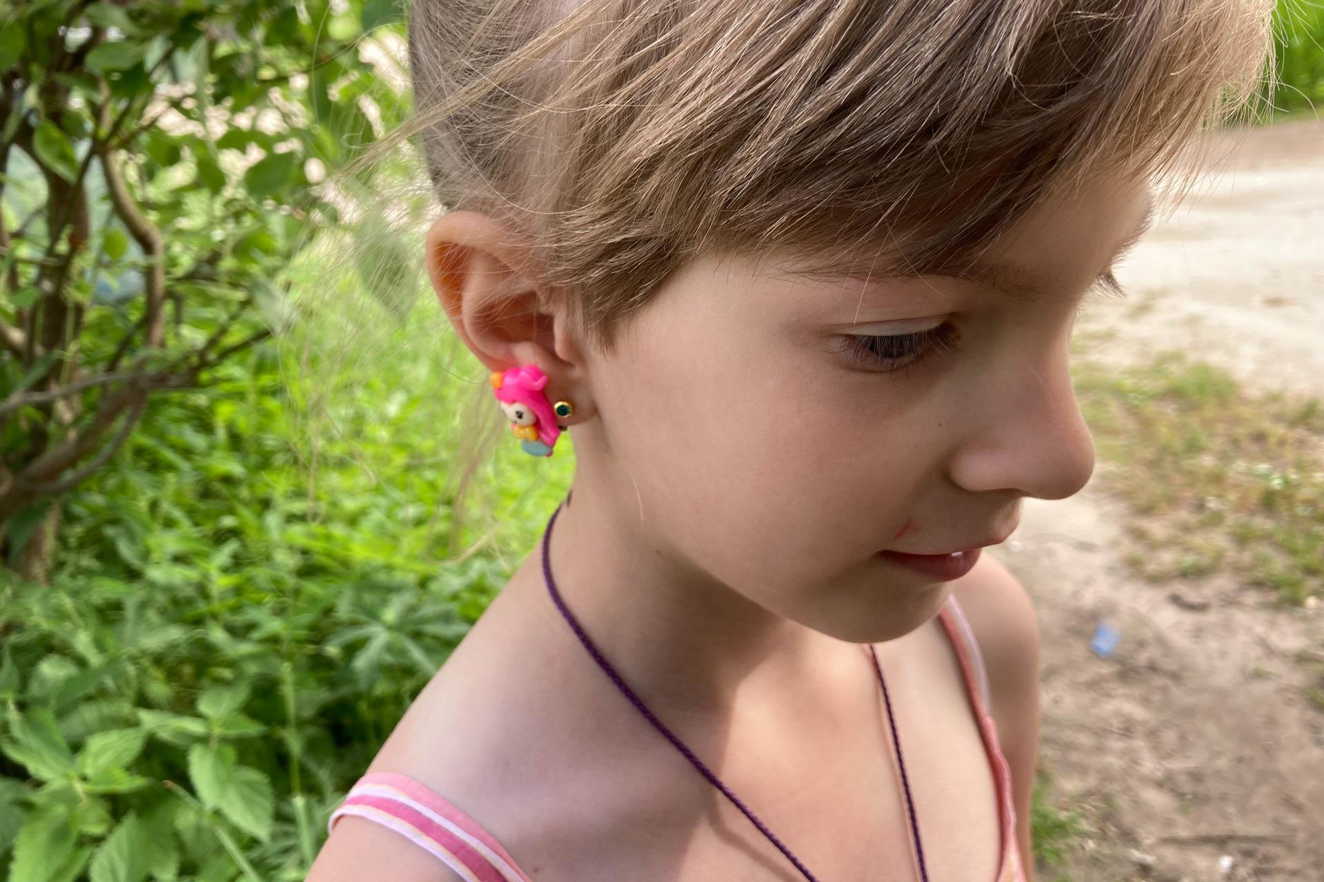Это подруга. У нее на ушах розовые клипсы. Их ей просто дали померить. Она довольна. Готова сфотографироваться.