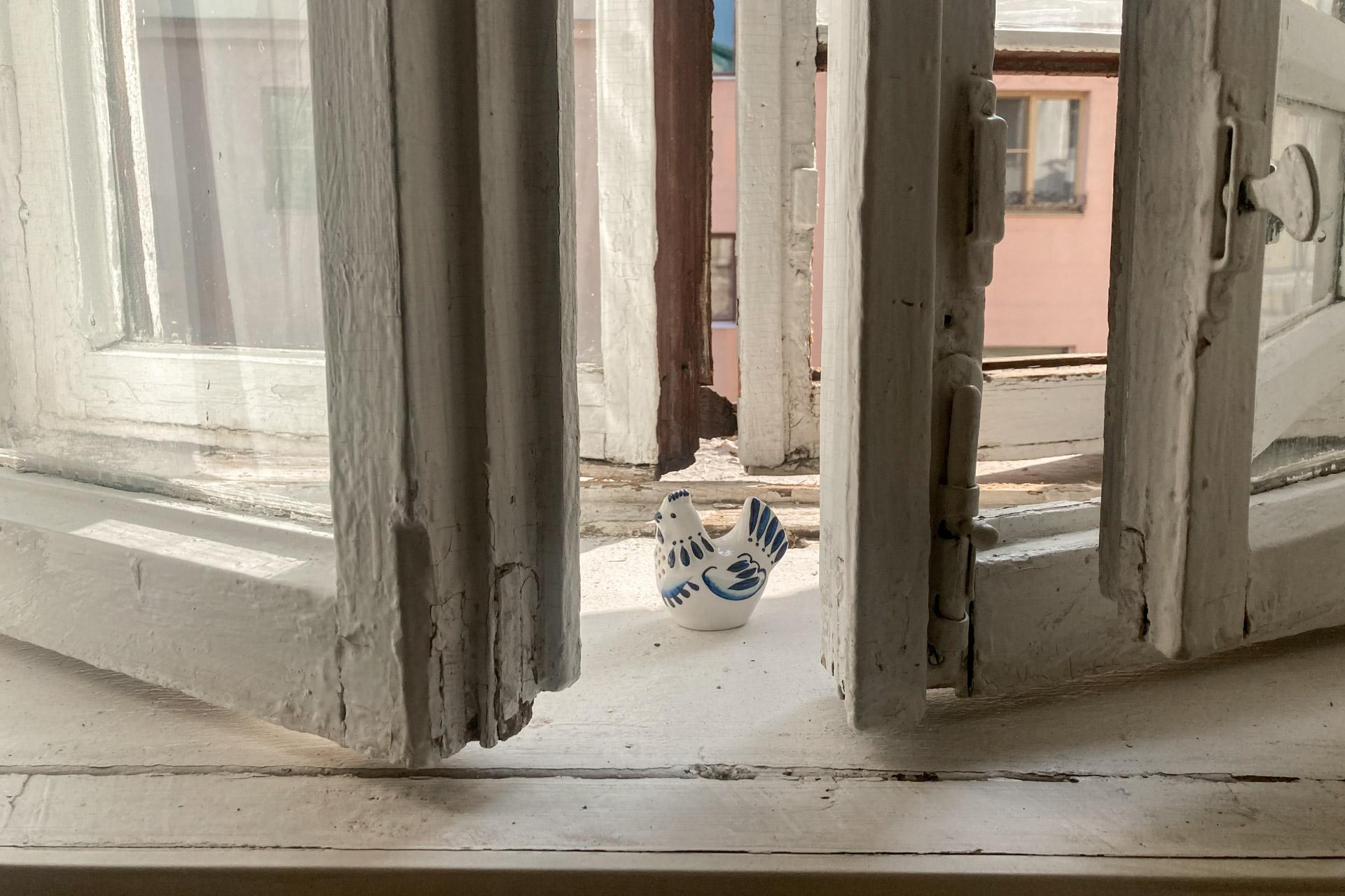 На фотографии окно. Это 3 этаж квартиры старого дома в Нижнем Кисловском переулке. За окном лето, середина августа 2021 года. Тепло. Окно открыто и на подоконнике стоит фигурка курочки из гжели.