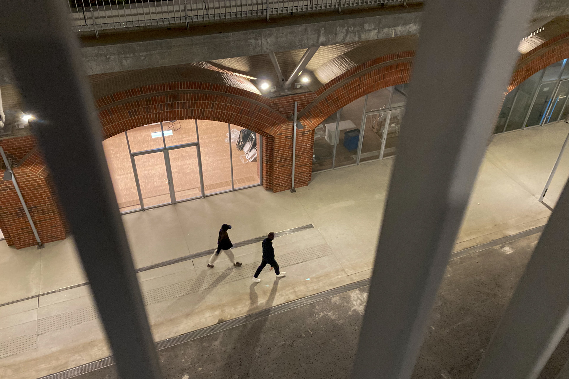 На фотографии парень и девушка. Они идут мимо новых сооружений на территории ГЭС-2. Он в черном, белые кеды, она в черной кепке и белых просторных брюках. Конец лета, вечер. Этот альбом создан, чтобы опубликовать эту фотографию на сайте. Эти двое еще на двух фотографиях будут идти.